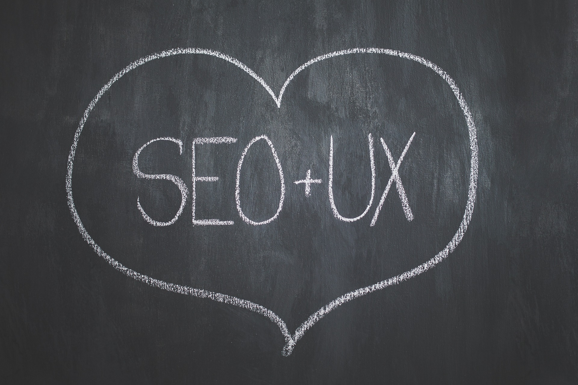 Heart containing the words SEO and UX on a blackboard