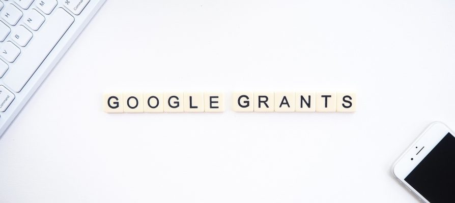 Letters of Google Grants next to a keyboard and a smartphone